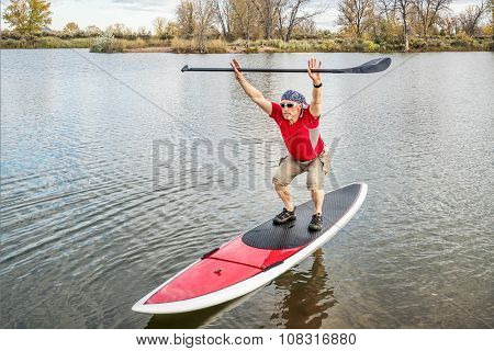 senior male paddler stretching and warming up on a paddleboard before paddling workout on a lake in Colorado