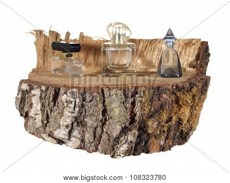 Three Empty Bottle Of Perfume On A Piece Of Birch Trunk Isolated On White Background.