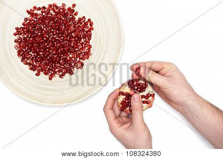Full plate of peeled pomegranate seeds and a man de-seeding granate