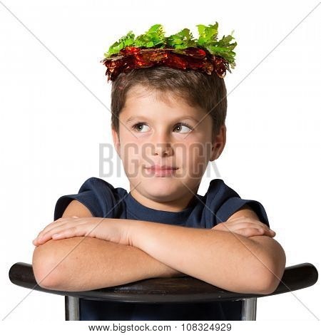 Boy sits astride a chair. Very beautiful seven year old boy in carnival wearing a crown of shiny green and red leaf