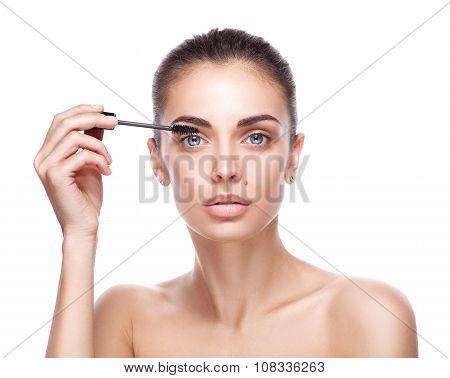 woman applying mascara makeup on eyes by brush