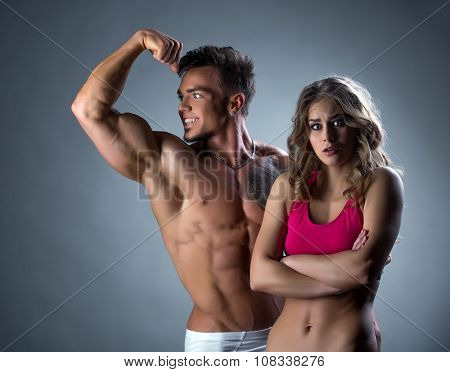Man admiring biceps and his girlfriend outraged