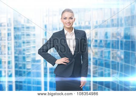 Portrait of businesswoman with her hand on hip, blue background. Concept of leadership and success