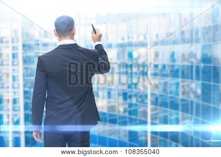 Backview of businessman writing with marker on imaginary screen, blue background. Concept of leadership and success