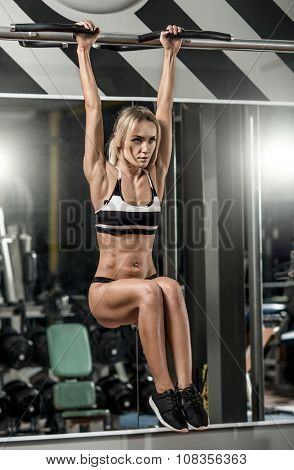 young fitness woman execute exercise on horizontal bar in gym vertical photo