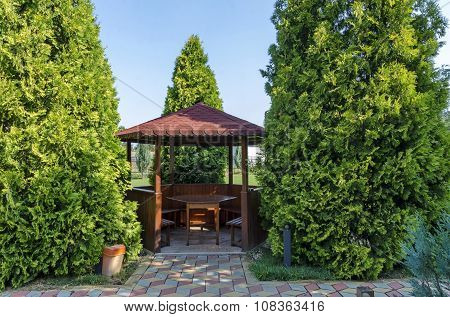 Beauty green yard with alcove with table wooden and bench for rest
