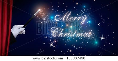 Magician hand performing trick with shiny Merry Christmas text