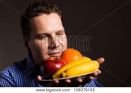 Diet and nutrition. Happy young man smelling fruits on dark gray. Guy recommending healthy nutrition. poster