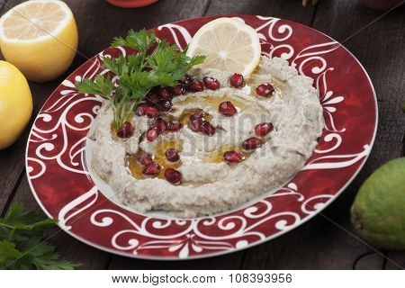 Baba ghanoush, levantine eggplant dish garnished with pomegranate seed, lemon and olive oil