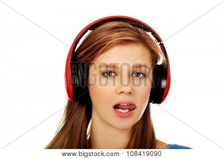 Teenage woman listens to music and shows tounge.