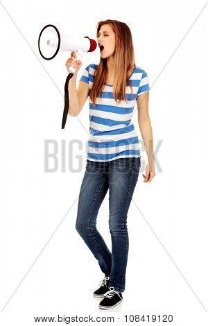 Teenage woman screaming through megaphone.
