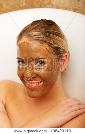 Happy spa woman with chocolate mask on face.