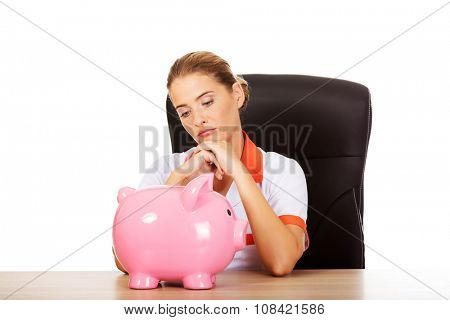 Young female doctor or nurse sitting behind the desk and holding a piggybank.