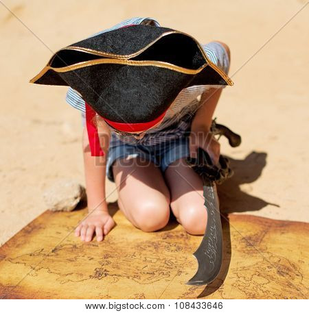 Little Girl In Pirate Costume With Sword Looking On The Map.