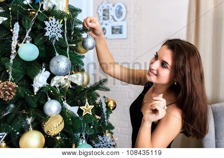 Beautiful Woman In A Black Dress Decorates A Christmas Tree