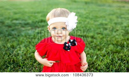 Cute little girl in the grass with red dress