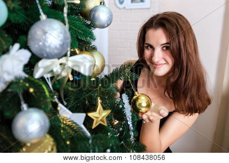 Smiling Girl In A Black Dress Decorates A Christmas Tree