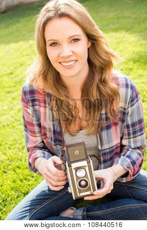 Young woman using her antique camera outside in the grass