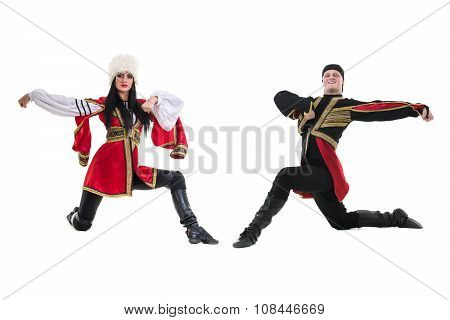 young couple wearing a folk costume dancing against isolated white background with copyspace poster