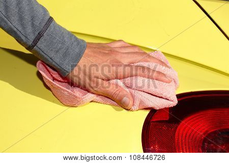 Hand with cloth washing a car. Waxing and polishing. poster