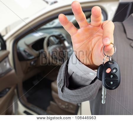 Hand with a car key. Auto dealership and rental concept background.