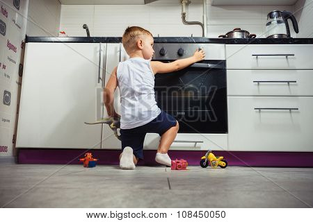 Child Playing In The Kitchen With A Gas Stove.