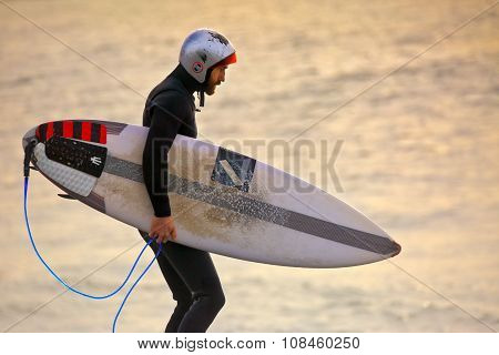 Surfer Wearing Gath Surf Helmet And Wetsuit At Sunrise