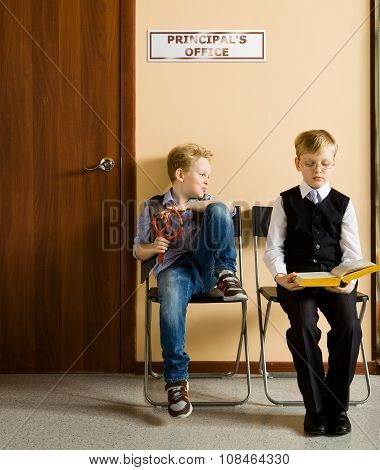 Schoolboys are sitting beside the principal's office in school