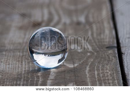 Glass transparent crystal glass ball on dark wooden background. Soft focus. With empty space for tex