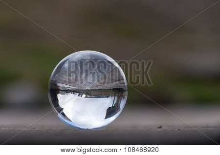 Glass transparent crystal ball on dark green background and wooden surface. Soft focus. With empty s