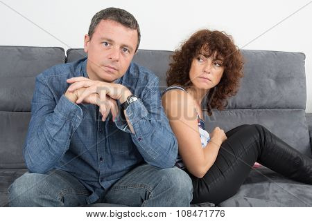 Bored Couple Sitting On The Couch At Home