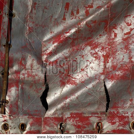Red and silvery stained ragged shabby cloth.  Grunge texture of threadbare synthetic material.