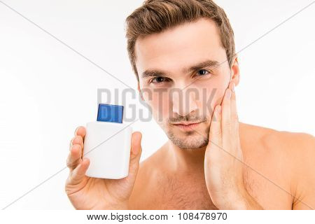 Handsome young man holding lotion after shave touching face poster