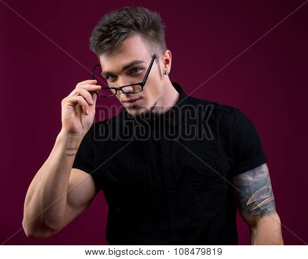 Portrait of sexy bodybuilder took off his glasses