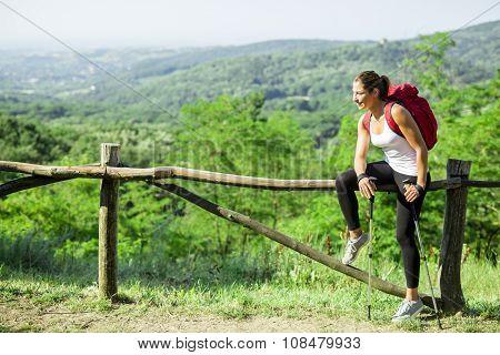 Beautiful hiker woman enjoying the view of a stunning green landscape below her poster