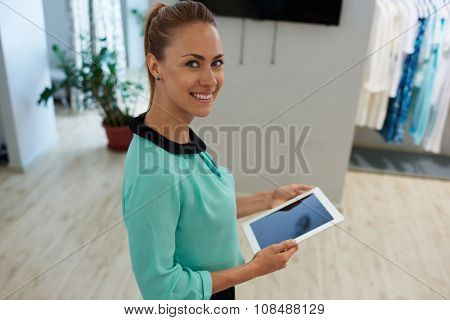 Smiling female seller using digital tablet while standing in shop