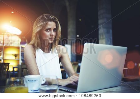 Portrait of gorgeous Sweden woman sitting with open laptop computer in modern coffee shop interior