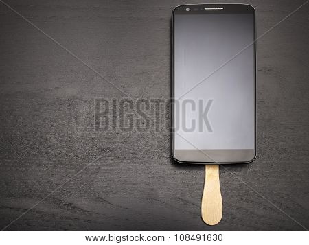 Mobile Phone On A Stick Like A Chocolate Popsicle On A Dark Background