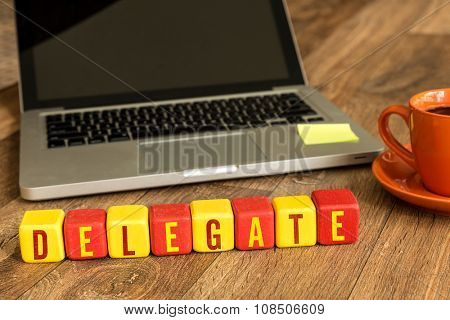 Delegate written on a wooden cube in a office desk