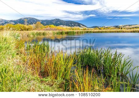 A beautiful reservoir in autumn fields at the foot of the Bridger mountain range in Cherry Creek Nature Preserve on the outskirts of Bozeman Montana poster