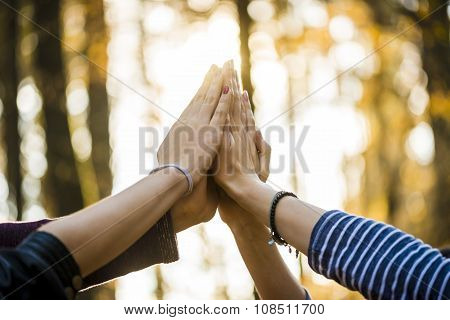 Closeup View Of Four People Joining Their Hands Together High Up In The Air