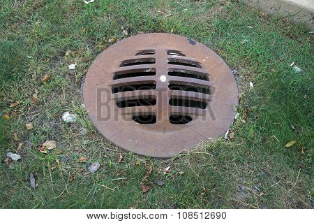 An iron storm drain cover allows storm water to drain away in Crest Hill, Illinois. poster