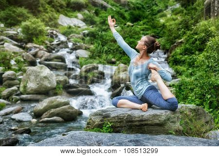 Young sporty fit woman doing yoga asana Eka pada rajakapotasana - one-legged king pigeon pose at tropical waterfall