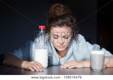 Unhappy tired woman with head on the table. Health issue, hangover or Monday morning concept.