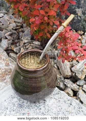 Yerba mate in a traditional calabash gourd and bombilla on the rock vertical
