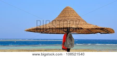 straw beach umbrella in the blue sky