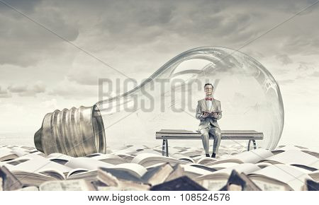 Young businessman inside of light bulb reading book