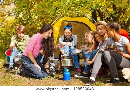 Teenagers cook soup in metallic pot near tent