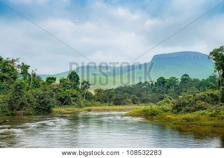 River In The Jungle. Small River In Jungle. Under The Cloudy Sky Through Hills And Mountains The Sma