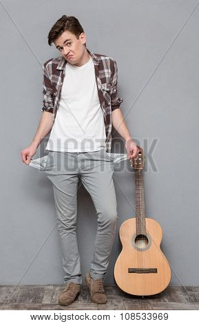 Full length portrait of a young man exhibiting his empty pockets on gray background